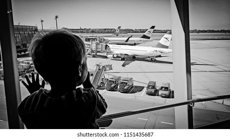 Vienna, Austria - August 31st 2016: Boy watches longingly the airplanes at the gates from the terminal through the window