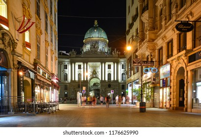 Vienna / Austria — August 7, 2013: night view of Kohlmarkt street and Michaelerplatz in the center of Vienna with the illuminated Hofburg palace, a former residence of Habsburg dynasty