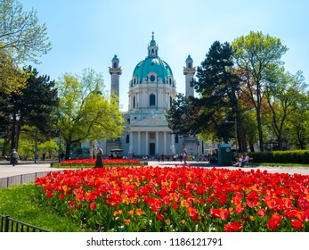 VIENNA, AUSTRIA - CIRCA APRIL 2018: View on the iconic Charles square as people pass by on the walkways in the park front of the historic building of Charles Church on a sunny day circa April 2018 in