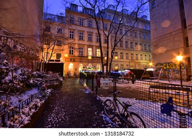 Vienna, Austria - Dec, 2018: Evening mood at snowy deserted park with children's playground at Spittelberg between historic houses of the old town in Advent. Some raindrops create atmospheric effect.