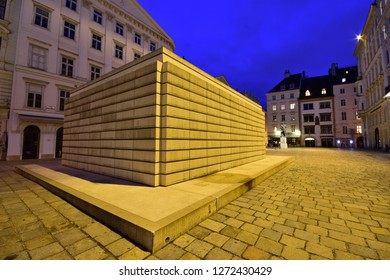 Vienna, Austria - Dec, 2018: Holocaust Memorial at illuminated Judenplatz town square stands for the Austrian Jewish victims of the Shoah, amongst medieval houses in the old town.