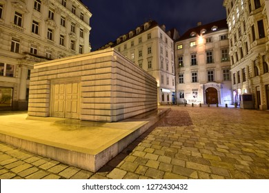 Vienna, Austria - Dec, 2018: Holocaust Memorial at illuminated Judenplatz town square stands for Austrian Jewish victims of the Shoah, amongst medieval and Wilhelminian style houses in old town.