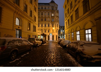 Vienna, Austria - Dec, 2018: Nocturnal illuminated cobblestone street in Vienna's historic old town with Gründerzeit houses and snow capped parked cars.