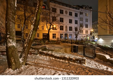 Vienna, Austria - Dec, 2018: Snowy park with trees, park benches and playground in front of a school surrounded by Gründerzeit buildings in old town on a winter evening.