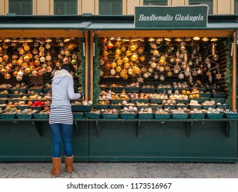 Vienna, Austria - December 01 2011: Shop keeper attending to her Christmas decorations for sale at the Christmas market in the grounds of Schonbrunn Palace, Vienna.