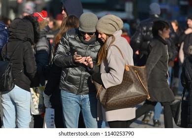 Vienna, Austria - December 16, 2016 : couple using smartphone and walking around crowd people in the Old city center of Vienna in Stephansplatz, Austria.