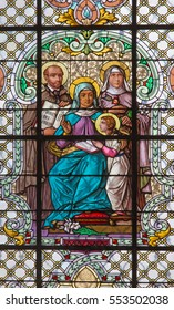 VIENNA, AUSTRIA - DECEMBER 19, 2016: The St. Ann with the st. Theresia and St. Ignace on the stained glass of church Mariahilfer Kirche by prof. Rudolf Geyling (1897) in workroom Carl Geylings Erben.