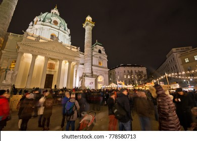 VIENNA, AUSTRIA - DECEMBER 19, 2017: Famous Christkindlmarkt at Karlsplatz with crowd of tourists and people in festive mood in Christmas time. Karlskirche (St. Charles's Church) in background.