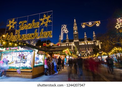 Vienna, Austria - December, 2017: Famous Christkindlmarkt christmas fair at Rathausplatz with tourists and people in festive mood in Advent. Town hall in background.