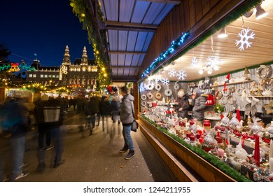 Vienna, Austria - December, 2017: Famous Christkindlmarkt christmas fair booth at Rathausplatz with tourists and people in festive mood in Advent. Town hall in background.