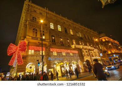 Vienna, Austria - December 2017: Huge red sparkling bow on the facade of a historic palace in Vienna at night. Decoration red bow on a building facade in front of the opera theater in Vienna, Austria.