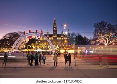 Vienna, Austria - December, 2017: Rathausplatz and town hall at Christmas. People visit the Christkindlmarkt and wait at traffic light to cross the road as blurred tram passes by.