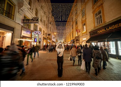 Vienna, Austria - December 2017: Tourist woman taking pictures at the Christmas decorations on Vienna busiest street