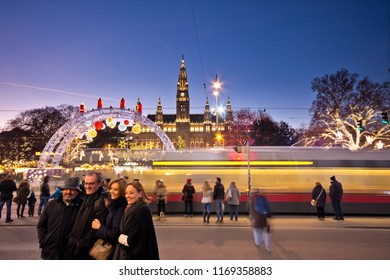 Vienna, Austria - December, 2017: View over Rathausplatz in Christmas time. Tourists posing for a group photo. A tram is passing by who want to cross the street. Famous town hall in background.
