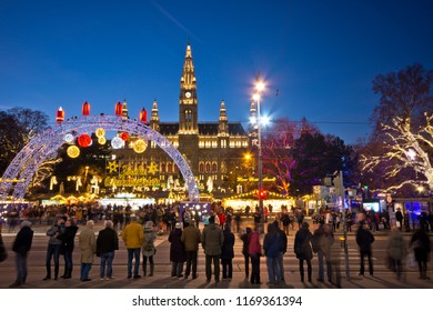 Vienna, Austria - December, 2017: View over Rathausplatz Christkindlmarkt in Christmas time. Visitors waiting at the traffic lights to cross the road. Famous town hall in background.