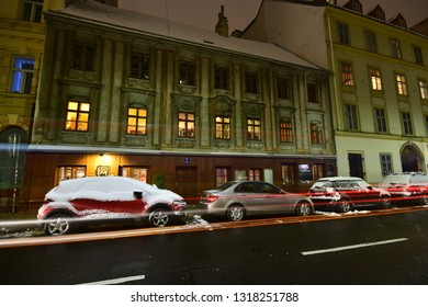 Vienna, Austria - December, 2018: Night mood with parked snowed cars and light trails on the street in front of a historic Baroque house in Advent.