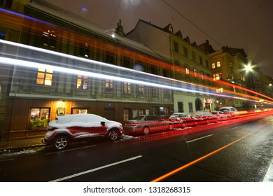 Vienna, Austria - December, 2018: Night traffic creates light trails on the street and parked snowed cars in front of historic Baroque house in winter.