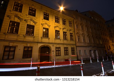 Vienna, Austria - December, 2018: Nocturnal illuminated street with car light trails in historic old town with baroque houses.