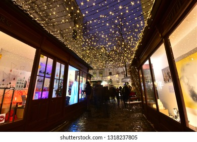 Vienna, Austria - December, 2018: Popular Christkindlmarkt Christmas market at Spittelberg with handicrafts in the displays under fairy lights in narrow street of the old town in Advent.