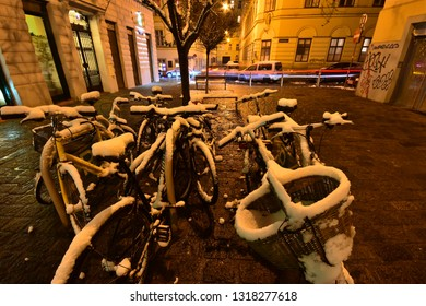 Vienna, Austria - December, 2018: Snow-covered bicycles at a parking lot on a paved square pedestrian area at night lighting and a passing car in the background generating a light trail.