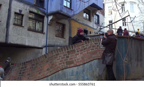 VIENNA, AUSTRIA - DECEMBER, 24, 2016 Father and his little son making photos near famous expressionist Hundertwasser House