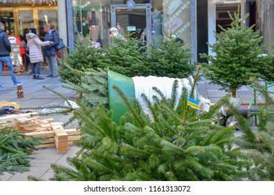 Vienna, Austria - December 24, 2017: Citizens of Vienna are choosing New year trees in the center of main Graben street on the Christmas eve.