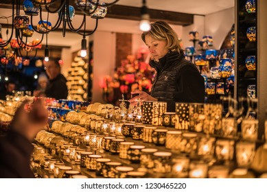 Vienna, Austria - December 24, 2017. Lighting colorful glass candle holders in kiosk at Viennese Christmas market. Close view of Xmas fair stall with seller selling craft souvenirs and candelabras.