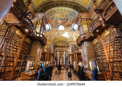 Vienna, Austria - December 24, 2017. Interior of Austrian National Library - old baroque library of Hapsburg empire located in Hofburg Palace. Grand Hall with lot of books and walking tourists.