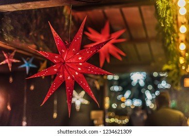 Vienna, Austria - December 25, 2017. Red light paper star lanterns hanging on string at Viennese Christmas Market. Close view of Xmas fair kiosk selling decorative luminous star lampshades.