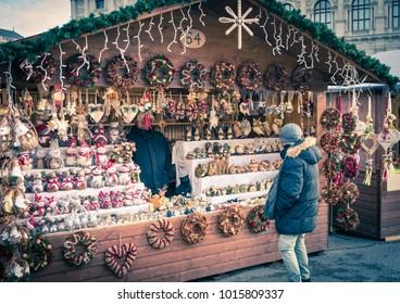 Vienna, Austria - December 28, 2017: Man standing in front of a festive kiosk which sells Christmas decorations, at the Maria-Theresien-Platz Christmas market, Vienna, Austria