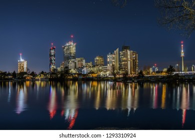 Vienna, Austria - December 29, 2017. Evening view of Donau City or Vienna DC with Andromeda Tower and modern architecture buildings reflected in water. Danube canal with illuminated business district.