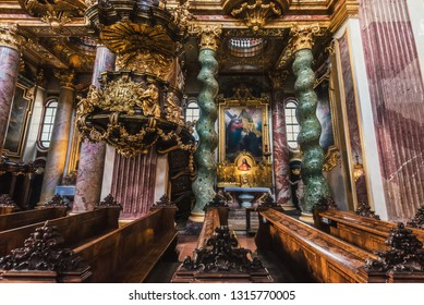Vienna, Austria - December 31, 2017. Interior of Jesuit Church or University church with decorated pulpit, wooden pews, ersatz marble columns, gilding, frescoes, wood carvings and paintings.