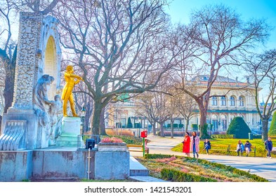 VIENNA, AUSTRIA - FEBRUARY 18, 2019: The group of tourists making selfies and photos with the Golden Strauss statue in City park, on February 18 in Vienna.