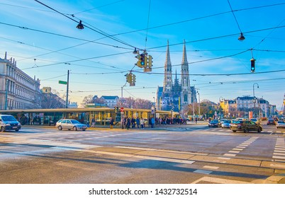 VIENNA, AUSTRIA - FEBRUARY 18, 2019: The traffic in intersection of Schottengasse and Ringstrasse with a view on Gothic Votive church on background, on February 18 in Vienna.