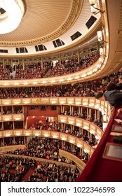 VIENNA, AUSTRIA - FEBRUARY, 2018: Interior of the Vienna State Opera auditorium with audience. Man looking down from the lateral upper tier seats.