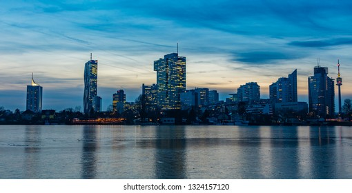 Vienna, Austria, February 7 ,2019: modern skyline of Vienna with UNO City reflected at night in the frozen Danube