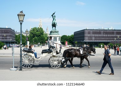 VIENNA, AUSTRIA - JULY 13, 2018: Close up of tourists in a horse-drawn carriage called Fiaker at the imperial Hofburg palace in Vienna, Austria