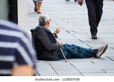 Vienna, Austria - July 16, 2018: senior foreign beggar sitting in shopping street of Kärntner Strasse. Around are walking people for shopping