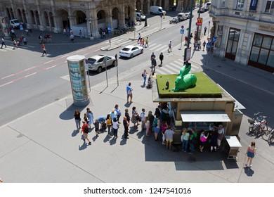 VIENNA, AUSTRIA - JULY 2018 : People queuing up at sausage stand, Bitzinger Wuerstelstand Albertina with big green rabbit on top on Albertinaplatz in Vienna, Austria on July 17, 2018.