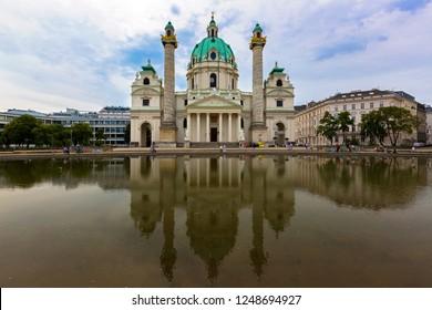 VIENNA, AUSTRIA - JULY 2018 : People walking near big pond in front of St. Charles Church, Karlsplatz in Vienna, Austria on July 15, 2018. It's called Karlskirche in Deutsch.