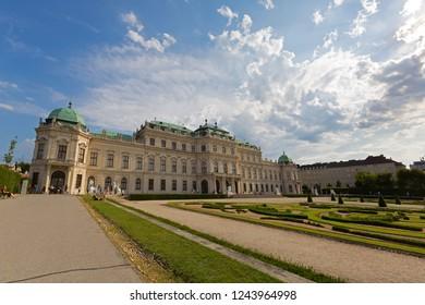 VIENNA, AUSTRIA - JULY 2018 : White Sphinx statue in garden with visitors sitting walking next by at Belvedere palace in Vienna, Austria on July 15, 2018.