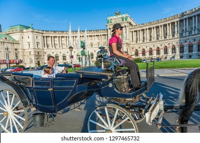 VIENNA, AUSTRIA - JULY 21, 2009:  people have a ride in the horsedrawn carriage called fiaker and passing the Vienna Hofburg in Vienna, Austria
