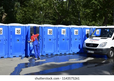 VIENNA, AUSTRIA - JULY 27, 2018: Man cleaning the portable public toilets at Karlsplatz, a park at Vienna city center