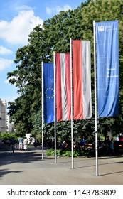 """VIENNA, AUSTRIA - JULY 27, 2018: Flags in front of TU Wien (Eng. """"Vienna University of Technology"""") at Karlsplatz. From left to right: European Union, Austria, Vienna, TU Wien"""