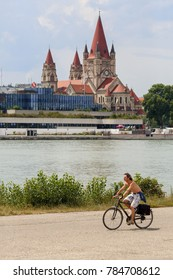 VIENNA/ AUSTRIA - JULY 9, 2017. A young man riding a bike on the Danube island, Donaustadt district. View of the Danube river and St. Francis of Assisi Church. Vienna, Austria.
