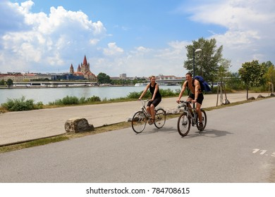 VIENNA/ AUSTRIA - JULY 9, 2017. A young couple riding bicycles on the Danube island, Donaustadt district. View of the Danube river and St. Francis of Assisi Church. Vienna, Austria.