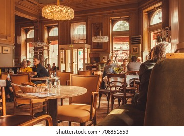 VIENNA, AUSTRIA - JUN 6, 2013: Dinner inside of dark room of historical cafe with talking people and vintage furniture on June 6, 2013. Vienna city has population near 1.8 million