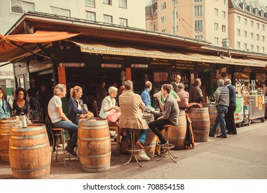 VIENNA, AUSTRIA - JUN 6: Barrels like tables and people around in cafe or bar in outdoor area of Naschmarkt, popular market of the city on June 6, 2013. Food and drinks market works from 1793