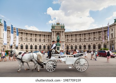Vienna, Austria - June 17 2018: Carriage passing in front of the Austrian National Library located in the Neue Burg Wing of the Hofburg in center of Vienna.