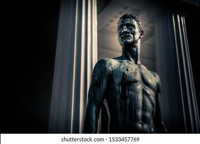 Vienna / Austria - June 29, 2019: Antonio Canova's work of Theseus bronze statue on the background of Theseus Temple columns in Vienna Volksgarten.